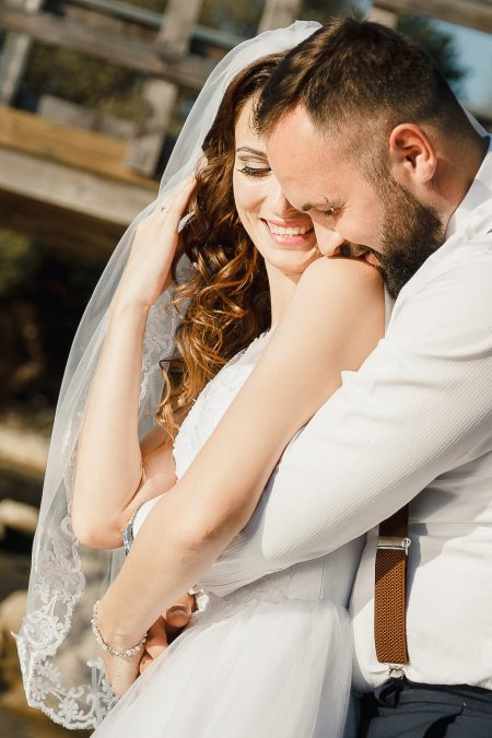 Wedding photography with bride and groom, close up with kiss on shoulder