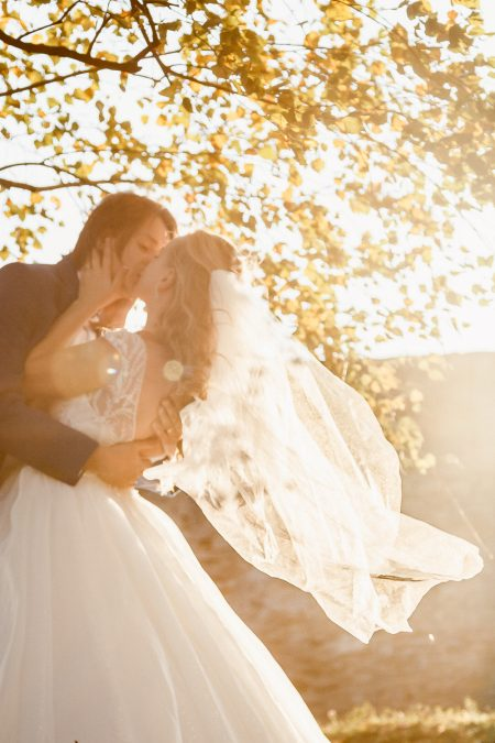 Beautiful wedding portrait of bride and groom kissing at sunset