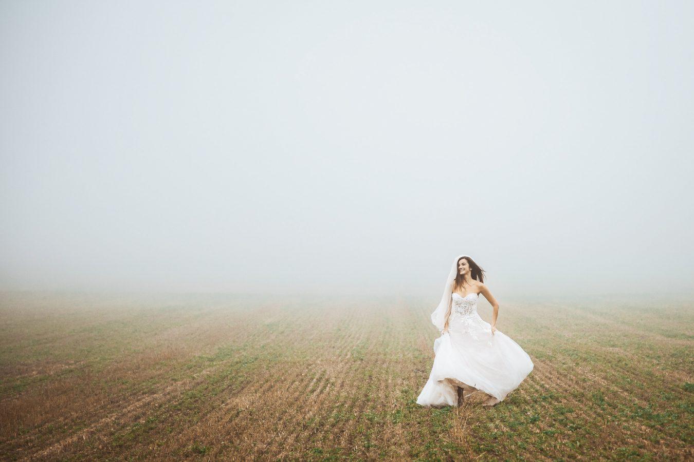 Bride running in fog Destination wedding photographers Peter and Ivana Miller