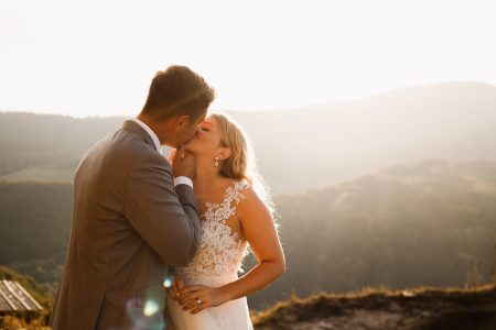 Bride and groom kiss at sunset in Slovak hills