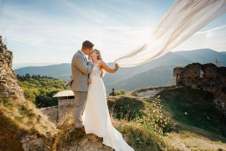 Bride holding veil kisses groom in Slovak hills