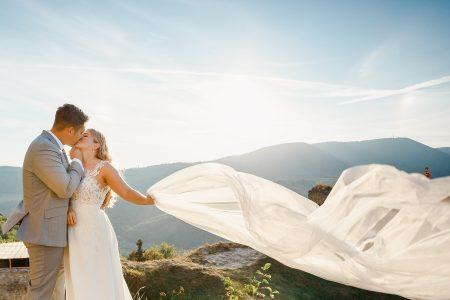 Bride holding wedding veil at sunset in Slovak hills Zborov