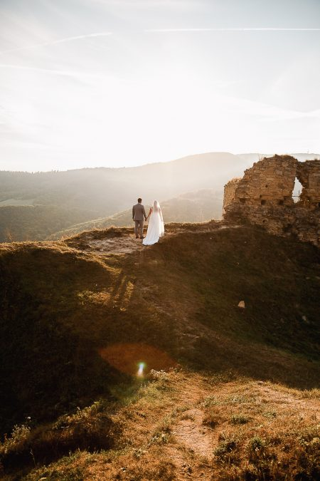 Beautiful sunset in Slovak hills with bride and groom holding each other