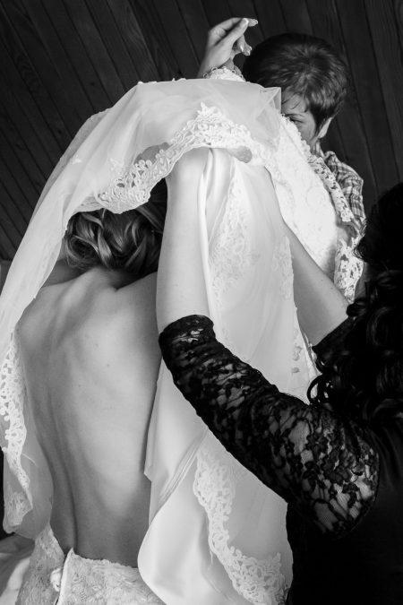 mum helping bride to get dressed