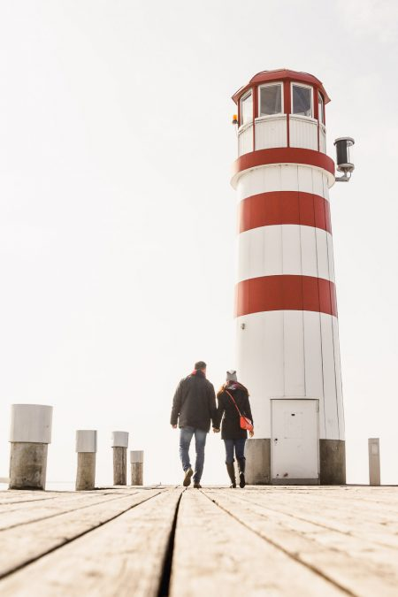 Husband and wife walking around frozen lake in Podersdorf am See, Austria_lighthouse in Austria